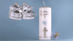 Baby shoes falling beside baptism candle on blue background Stock Footage