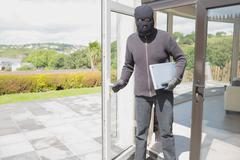Burglar holding laptop - stock photo