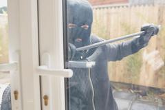 Burglar opening the door with a crowbar - stock photo