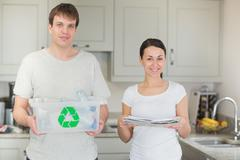 Couple holding recycling bin and newspapers - stock photo
