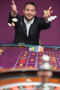 Man throwing chips onto roulette table Stock Photos
