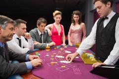 People looking at dealer dealing blackjack cards - stock photo