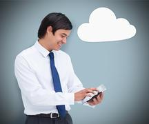 Businessman using a tablet pc with cloud computing symbol - stock photo