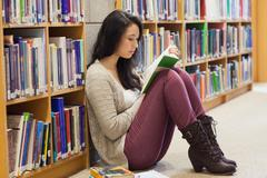 Student leaning against a shelf in a library - stock photo