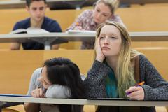 Demotivated students in a lecture hall Stock Photos