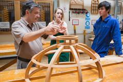Two students and an explaining teacher in a woodwork class Stock Photos
