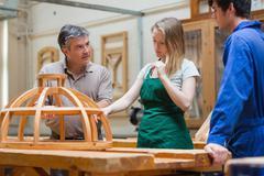 Teacher teaching a woodwork class - stock photo