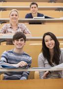 Happy students sitting in a lecture hall Stock Photos