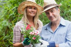 Stock Photo of Blonde woman and man holding potted plant
