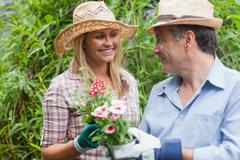 Man and woman holding a flower pot - stock photo