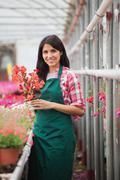 Garden center employee standing and holding flower pot Stock Photos