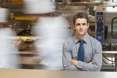 Waiter standing in busy kitchen - stock photo