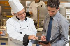 Head chef and waiter discussing menu - stock photo