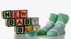 Blue soother falling besides slippers and baby blocks Stock Footage