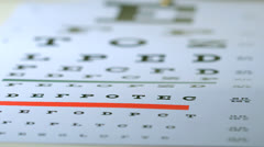 Reading glasses falling onto eye test Stock Footage