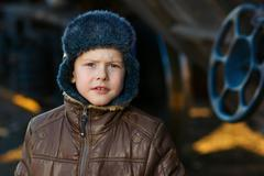 Boy bum homeless on street freezing close to railway carriage in Stock Photos