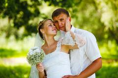 Couple newlyweds wedding are in green summer forest, bride and g Stock Photos