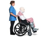 injured man in wheelchair with nurse - stock photo
