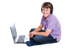 Stock Photo of schoolboy with laptop and headphones isolated