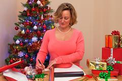 A woman at home wrapping christmas presents Stock Photos