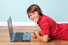 boy wearing headphones with laptop - stock photo