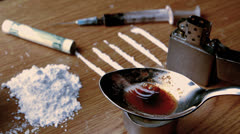 Drug cooking on a spoon surrounded by pile lines and syringe on wooden table Stock Footage
