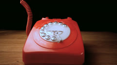 Red receiver falling onto retro dial phone Stock Footage