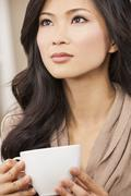 beautiful chinese oriental asian woman drinking - stock photo