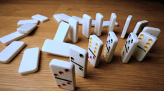 The domino effect on wooden table high angle shot Stock Footage