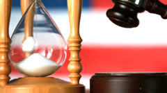Gavel dropping on sounding block beside hourglass Stock Footage
