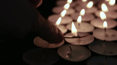 Hand lighting tea light candles with match Stock Footage