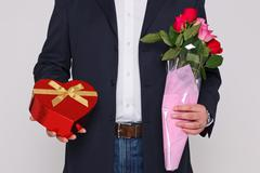 Man holding flowers and a box of chocolates Stock Photos