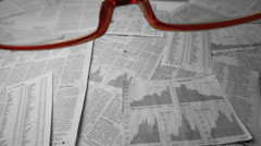 Glasses falling over sheets of paper showing graphs and data - stock footage