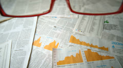 Glasses falling over sheets of paper showing yellow charts - stock footage