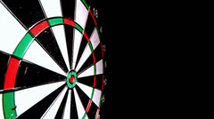 Red dart hitting the bulls eye on black background Stock Footage