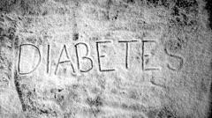Diabetes written into sugar powder being blown away Stock Footage