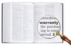 warranty through a magnifying glass over dictionary. - stock photo