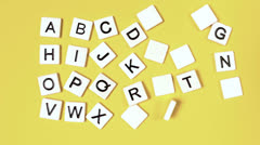 Stock Video Footage of Plastic letters bouncing and showing alphabet on yellow surface
