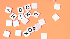 Stock Video Footage of Plastic letters bouncing and showing alphabet on orange surface