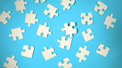 Jigsaw puzzle falling on blue surface Stock Footage