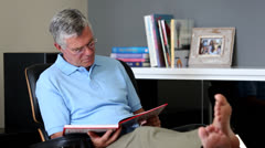 Barefoot man relaxing on a chair while reading a book Stock Footage
