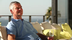 Man drinking a glass of wine while sunbathing Stock Footage