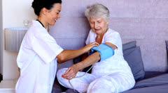 Home nurse checking patients blood pressure Stock Footage