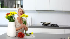 Woman arranging flowers and holds one to husbands nose Stock Footage
