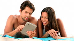 Couple relaxing on the beach with a tablet Stock Footage