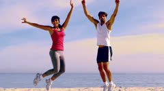 Couple jumping with hands up Stock Footage