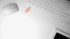Paperclip falling in the middle of an office desk - stock footage