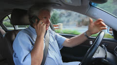 MAN TALKS ON CELL PHONE WHILE DRIVING - stock footage
