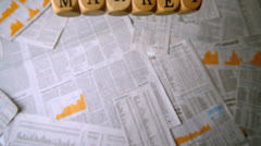 Wooden dice spelling out stock market falling over sheets of paper Stock Footage