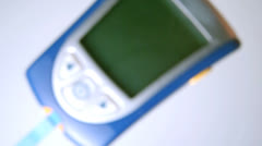 Blood glucose monitor falling on white surface Stock Footage